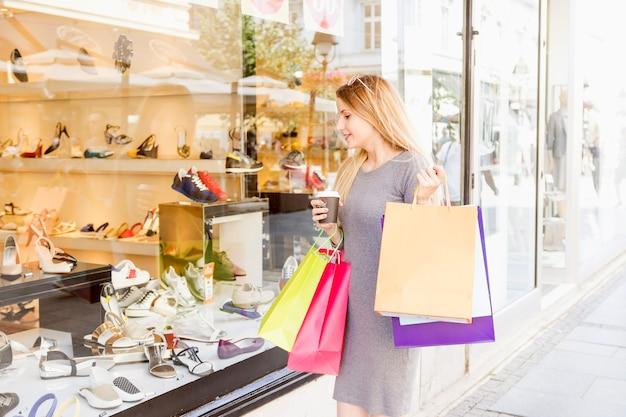 Mujer joven con coloridos bolsos de compras haciendo escaparate de compras Foto gratis
