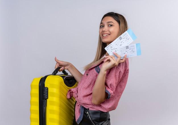 Una mujer joven complacida con camisa roja sosteniendo una maleta amarilla con boletos de avión mientras mira en una pared blanca Foto gratis