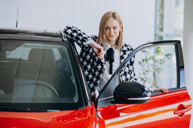 Mujer joven comprando un automóvil en una sala de exposición de automóviles Foto gratis