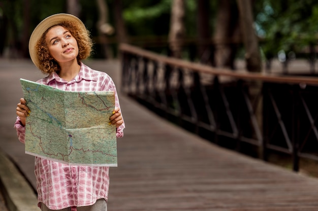 Mujer joven comprobando un mapa de un nuevo destino con espacio de copia Foto gratis