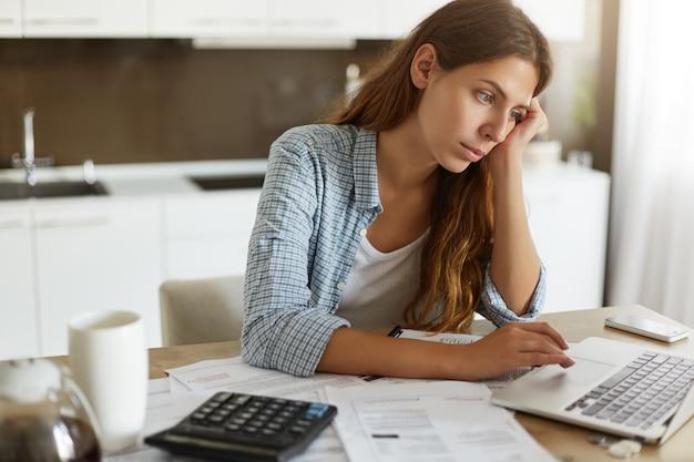 Mujer joven comprobando su presupuesto y haciendo impuestos Foto gratis