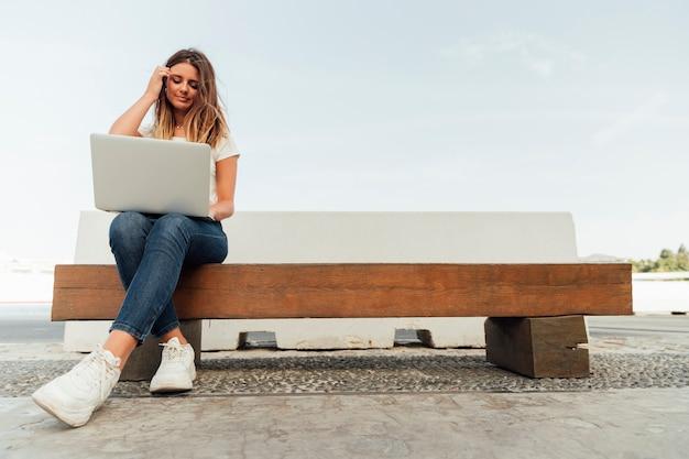 Mujer joven con una computadora portátil en un banco Foto gratis
