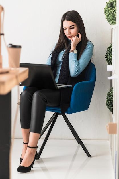 Mujer joven con la computadora portátil en la silla Foto gratis