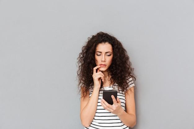 Mujer joven concentrada que usa un teléfono inteligente y se toca los labios frustrada o recibe malas noticias sobre la pared gris Foto gratis