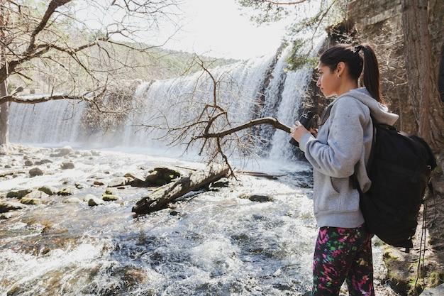 Mujer joven concentrada sujetando unos prismáticos Foto Gratis