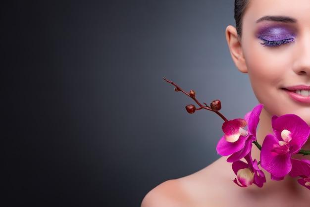 Mujer joven en concepto de belleza con flor de la orquídea Foto Premium