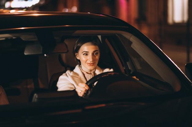 Mujer joven, conducción, en coche, por la noche Foto gratis