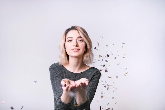 Mujer joven con confeti volador Foto gratis