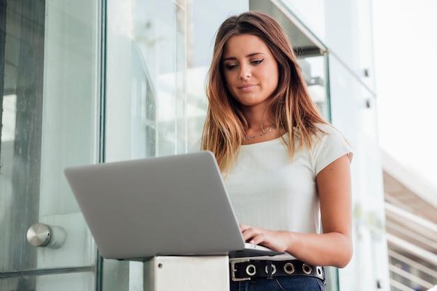 Mujer joven confidente navegando portátil Foto gratis