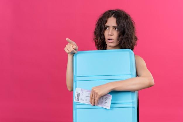 Una mujer joven confundida con pelo corto vistiendo verde crop top apuntando con el dedo índice sosteniendo la maleta azul con billetes de avión Foto gratis