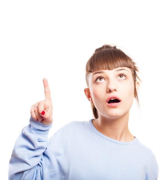 Mujer joven confusa con la boca abierta mirando hacia arriba Foto Gratis