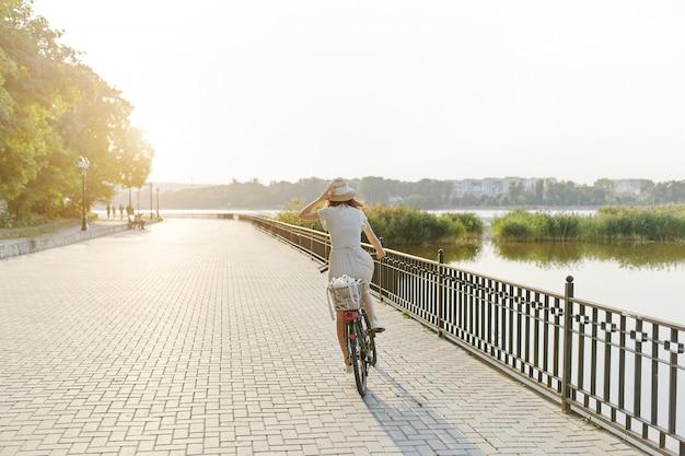 Mujer joven contra el fondo de la naturaleza con bicicleta Foto gratis