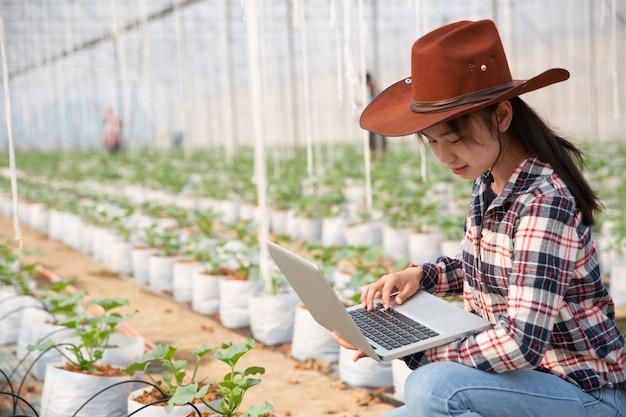 Mujer joven controlando una plantación Foto gratis