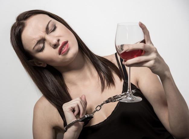 Mujer joven con una copa de vino y esposas. Foto Premium