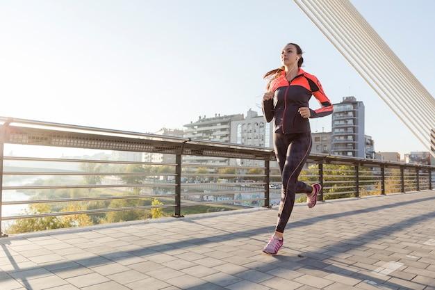Mujer joven corriendo al aire libre Foto gratis