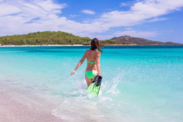 Mujer joven corriendo hacia el mar tropical azul con equipo de snorkel Foto Premium