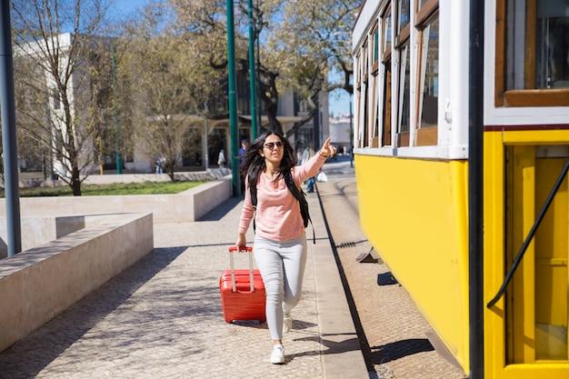 Mujer joven corriendo tras un trolebús y tirando de una maleta. Foto gratis