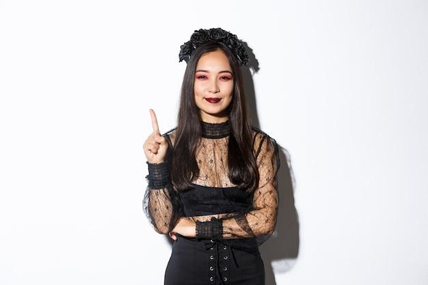Mujer joven creativa en traje de bruja sonriendo complacida al tener una gran idea, levantando el dedo para decir sugerencia. mujer asiática vestida como viuda o mago misterioso, fondo blanco. Foto gratis
