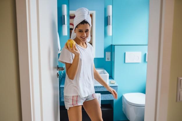 Mujer joven, en, cuarto de baño, tenencia, manzana | Foto ...