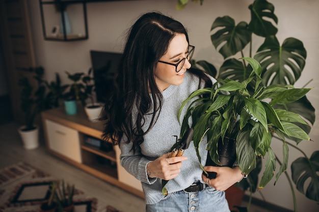 Mujer joven cultivando plantas en casa Foto gratis