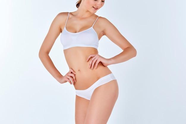 Mujer joven, delgada, sana y hermosa en lencería blanca Foto gratis