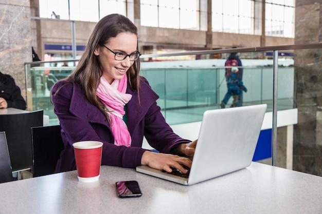Mujer joven dentro de la estación de tren o aeropuerto Foto Premium