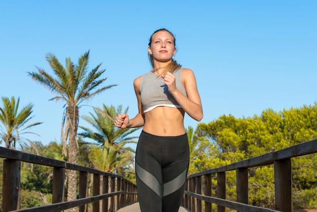 Mujer joven del deporte que hace ejercicio y que corre en el parque Foto Premium