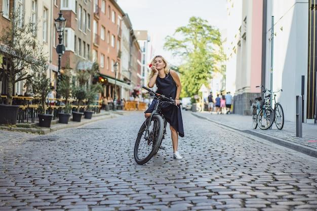 Mujer joven de los deportes en una bicicleta en una ciudad europea. el deporte en entornos urbanos. Foto gratis