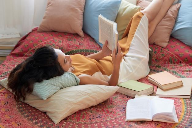 Mujer joven descansando con el libro en la cama con las piernas sobre las almohadas Foto gratis