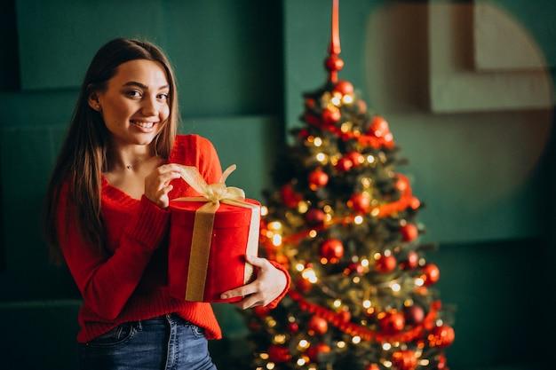 Mujer joven desempacando el regalo de navidad junto al árbol de navidad Foto gratis