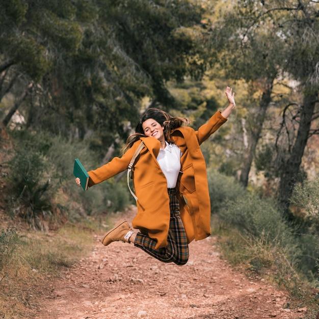 Mujer joven despreocupada que sostiene el libro en la mano que salta en rastro de montaña Foto gratis