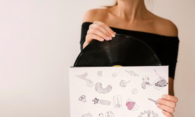 Mujer joven con disco de vinilo en su estuche Foto gratis