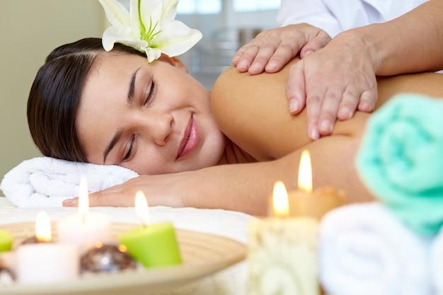 Mujer joven disfrutando de un masaje de hombros Foto gratis