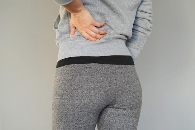 Mujer joven con dolor en los riñones. mujer con dolor de espalda juntando su mano a su espalda baja. Foto Premium