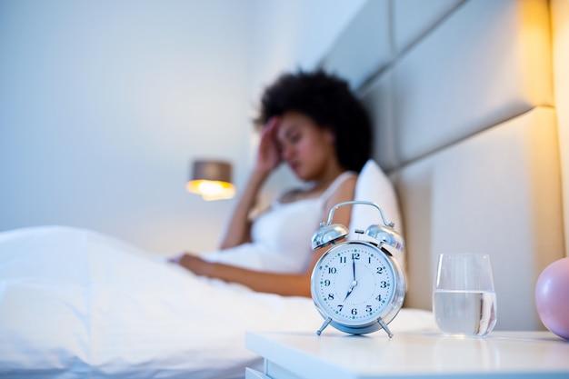 Mujer joven en el dormitorio de su casa acostada en la cama a altas horas de la noche tratando de dormir sufriendo trastorno del sueño insomnio o asustada por las pesadillas con cara de tristeza, preocupación y estrés Foto Premium