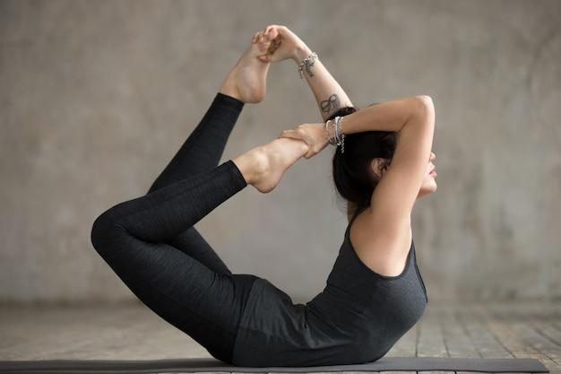 Mujer joven en ejercicio de arco Foto gratis