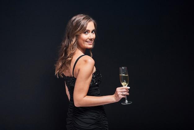 Mujer joven en elegante vestido con copa de champán contra negro Foto Premium