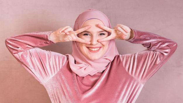 Mujer joven emocionada que gesticula la muestra de v cerca de los ojos que miran la cámara Foto gratis