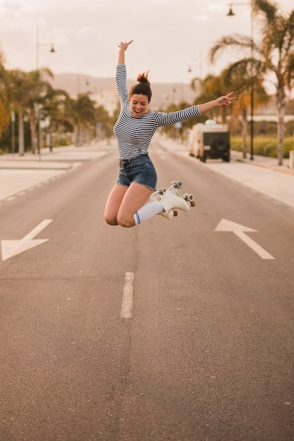 Mujer joven emocionada que gesticula el signo de la paz que lleva el patín de ruedas que salta en el camino Foto gratis