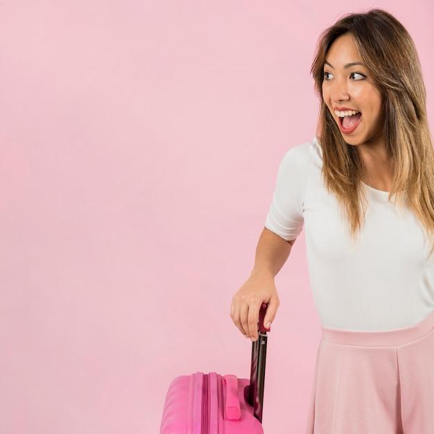 Mujer joven emocionada que lleva la maleta del viaje contra fondo rosado Foto gratis