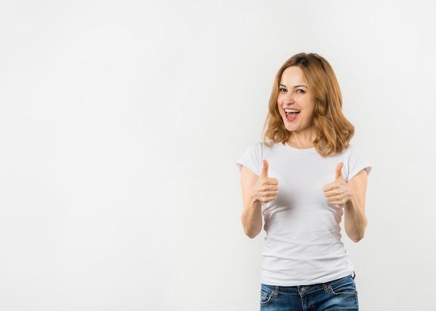 Mujer joven emocionada que muestra el pulgar encima de la muestra aislada en el contexto blanco Foto gratis