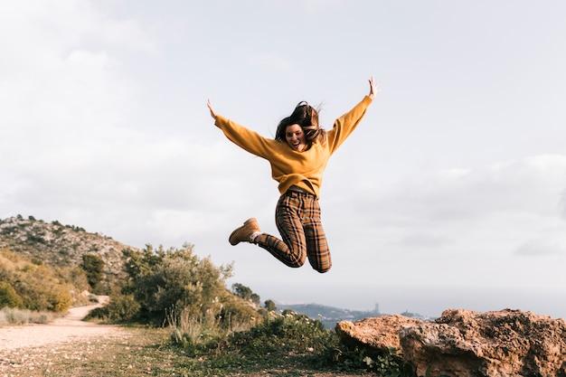 Mujer joven emocionada que salta en la montaña Foto gratis