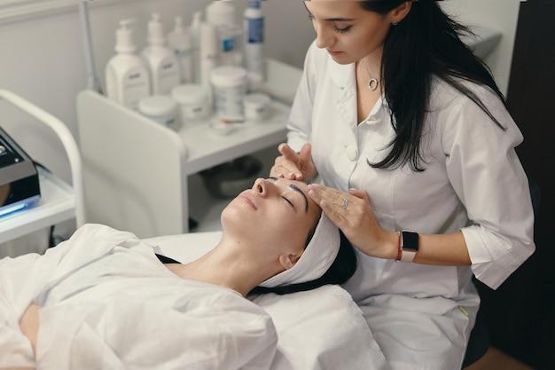 Mujer joven se encuentra con los ojos cerrados, cosmetóloga haciendo procedimiento Foto gratis