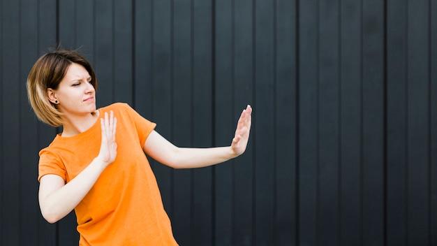Mujer joven enojada que muestra gesto de la parada contra fondo negro Foto gratis