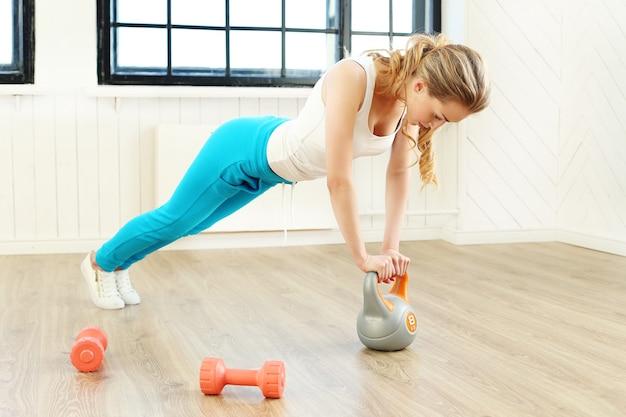 Mujer joven entrenando en el gimnasio Foto gratis