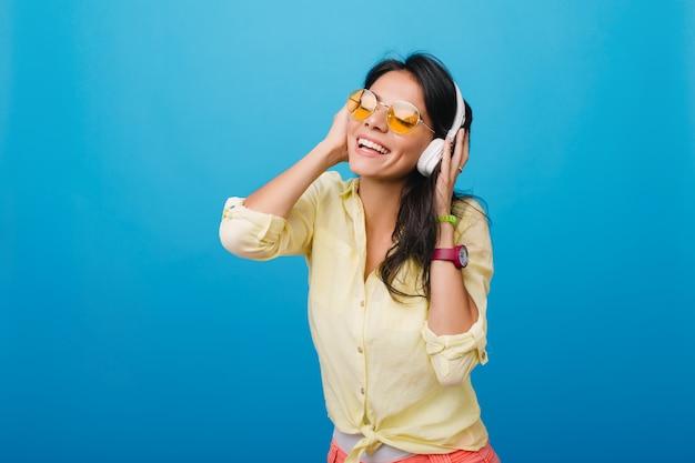 Mujer joven entusiasta en elegante camisa amarilla y pulsera rosa tocando auriculares mientras disfruta de la canción. foto de interior de dichosa niña hispana con cabello castaño oscuro brillante posando. Foto gratis