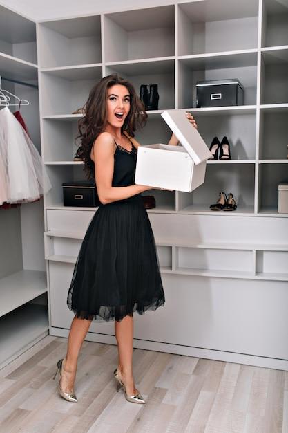 Mujer joven entusiasta se encuentra en un elegante armario con una caja abierta en sus manos. está vestida con un vestido negro y zapatos plateados. emociones asombrosas. Foto gratis