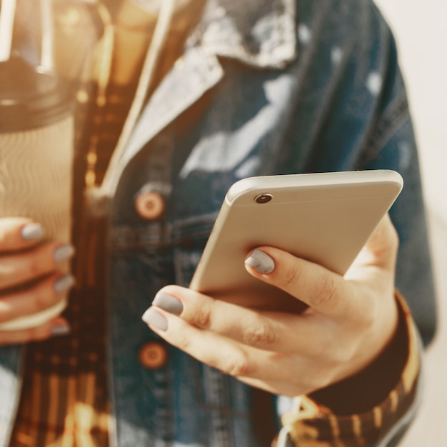 Mujer joven enviando mensajes de texto caminando por una calle de la ciudad Foto Premium