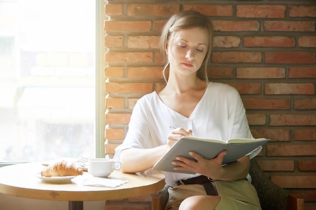 Mujer joven escribiendo en un planificador en la mesa de café en la mañana Foto gratis