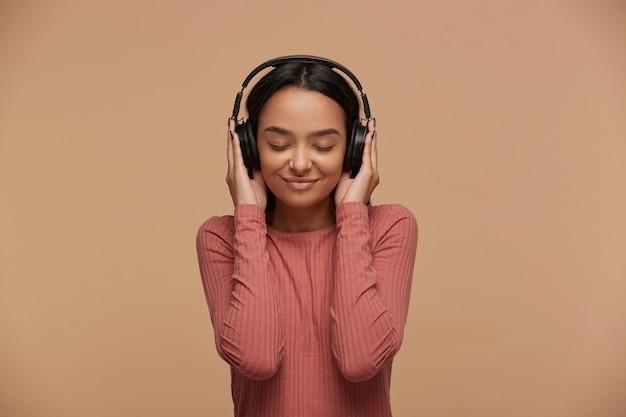 Una mujer joven escucha su música favorita en grandes auriculares negros Foto gratis